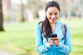 Asian student texting on the phone — Stock Photo