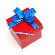 Red gift box with blue bow - Stock Photo