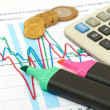 Calculator, coins and pen laying on chart. - Stock Photo