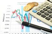 Calculadora, monedas y colocación en la tabla de la pluma. — Foto de Stock