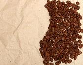 Kávová zrna na starý papír — Stock fotografie