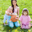 Three children sitting on the grass — Stock Photo #5780391