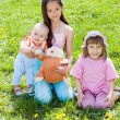 Three children sitting on the grass — Stock Photo