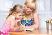 Madre con un niño dibuja — Foto de Stock