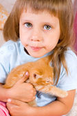 Girl hugs ginger kitten — Stock Photo