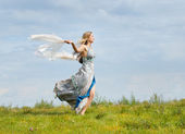 Young girl runs across the field — Stock Photo