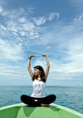 Pretty young woman performs as yoga move in-front of boat during holiday to — Stock Photo