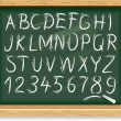 Alphabet and numbers on a blackboard — Stock Vector
