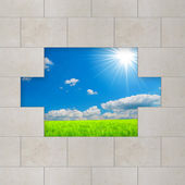 Grey wall to see green field and blue sky — Stock Photo