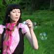 Stock Photo: Womblowing soap bubbles