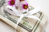 Dollars with flowers and bow — Stock Photo