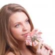 Pretty young woman smelling a pink flower — Stock Photo