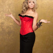 Sexy blonde woman in red corset and skirt on golden background — Stock Photo