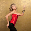 Sexy blonde woman in red corset and skirt on golden background - Stock Photo