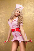 Sexy blonde woman in seductive pink nurse costume on golden back — Stock Photo