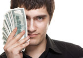 Young handsome man holding dollars — Stock Photo