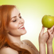 Young beauty woman with apple on green background - Stock Photo