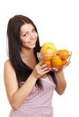 Happy woman holding a dish with fruits on white background — Stock Photo