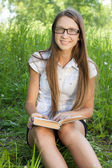 Young student girl sitting in park with book — Stock Photo
