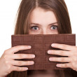 Shot of a beautiful teen girl holding big chocolate bar - Stock Photo