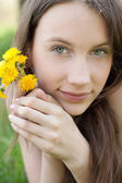 Young beautiful teenager with dandelion bouquet — Stock Photo