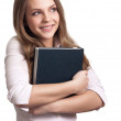 Attractive woman smiling while holding book — Stock Photo
