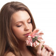 Closeup of a pretty young woman smelling a pink flower — Stock Photo