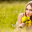 Beautiful young blonde woman on the meadow on a warm summer day — Stock Photo #5870958