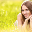 Beautiful young blonde woman on the meadow on a warm summer day — Stock Photo