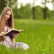 Stock Photo: Girl-student sit on lawn and reads textbook.