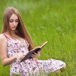Girl-student sit on lawn and reads textbook. — Stock fotografie