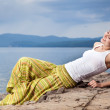 Beautiful happy woman sitting on rock over sea at summer storm d — Stock Photo