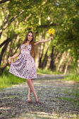Portrait of a beautiful blonde woman with yellow flowers outdoor — Stockfoto