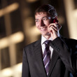 Happy businessman talking on cell phone at night city in the bac — Stock Photo