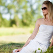 Young blond woman in white dress relaxing in the park — Stock Photo