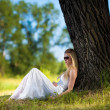 Stock Photo: Young blond woman in white dress relaxing in the park