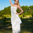 Young blond woman in white dress in the park — Stock Photo