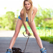 Young happy blond woman with dog on roller skates in the park — Stock Photo #6088413