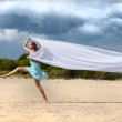 Beautiful young woman walking on the beach with a white tissue — Stock Photo #6088426