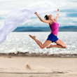 Royalty-Free Stock Photo: Beautiful young woman jumping on the beach with a white tissue