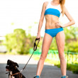 Young blond woman with dog on roller skates in the park — Stock Photo #6088517