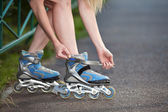 Young woman put on roller-skate close up — Stock Photo