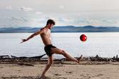 Starke sexy männlichen kick roten ball am strand — Stockfoto