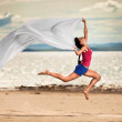 Beautiful young woman jumping on the beach with a white tissue — Stock Photo
