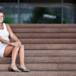 Stock Photo: Attractive young woman sitting on a staircase of an office build