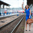 Attractive lady waiting train on the platform of railway station — Stock Photo