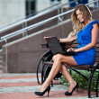 Attractive stylish lady with laptop sitting on a bench in the ci — Stock Photo