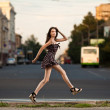 Stock Photo: Young carefree womjumping at street in city