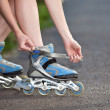 Young woman put on roller-skate close up - Foto Stock