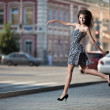 Royalty-Free Stock Photo: Young carefree woman jumping at the street in city